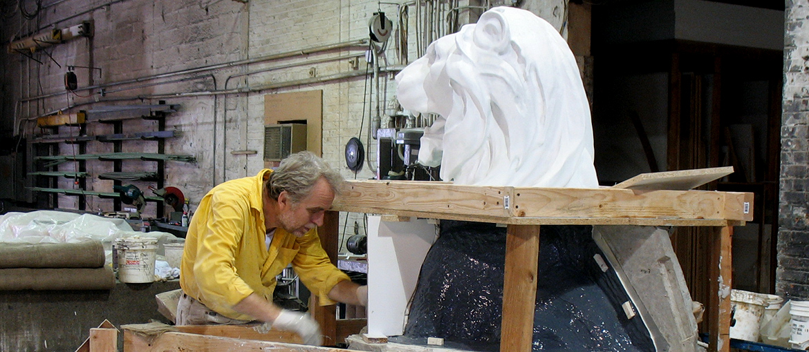 Man working on lion statue in shop